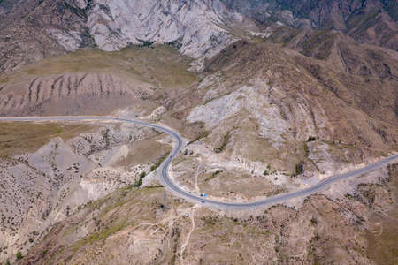 Aerial view of the winding asphalt road paved in the Altai Mountains through rocks with lots of stones, on a clear summer day. Travel in the mountains. Stok Fotoğraf