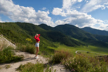 The girl in red top and blue shorts with a view of satisfaction reaches for the sun on the edge of a cliff in the Altai Mountains, below are green fields with trees and grass under a blue sky with clouds.