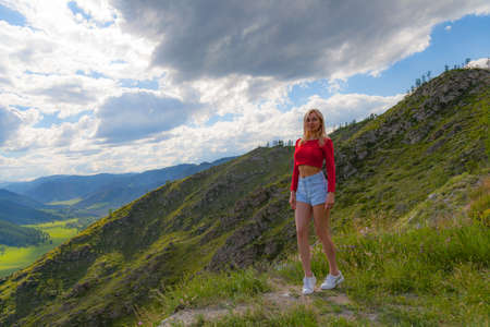 A girl in a red top and blue shorts on the edge of a cliff in the Altai Mountains, below are green fields with trees and grass under a blue sky with clouds.