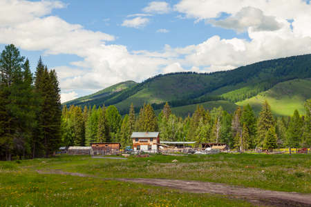 A picturesque place in the Altai Mountains with green trees and grass in the wild with a farm and houses under the blue sky with white clouds on a warm summer day. Stok Fotoğraf