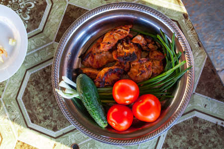 Flat lay of a silver plate with grilled golden pork or beef meat with burnt crust, green cucumbers, fresh red tomatoes and onions on the table