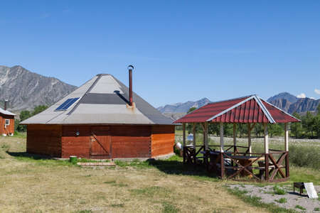 The ancient antique ail house from wood is round-shaped with a chimney on top of the center, for the nomadic indigenous people in the Altai Mountains with green trees and picturesque scenery.