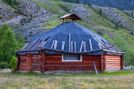 The ancient antique ail house from wood is round-shaped with a chimney on top of the center, for the nomadic indigenous people in the Altai Mountains with green trees and picturesque scenery. 版權商用圖片 - 126755987