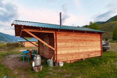 A simple wooden house for temporary living in the summer in the Altai Mountains with a chimney on the roof in a picturesque place with green grass and trees. Travel and nature.