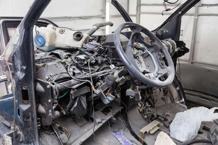 Car interior in the back of a van with a disassembled dashboard and view on steering wheel during preparation in a vehicle repair workshop. Auto service industry