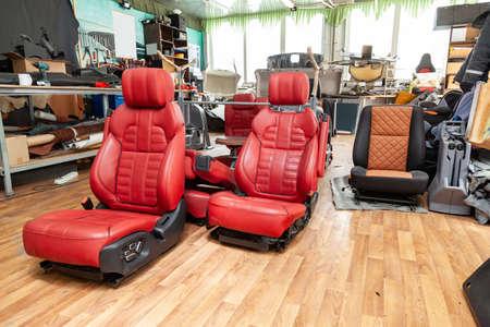 Cuatro asientos deportivos con tapizado de cuero rojo, ubicados en el piso del taller para reparación y puesta a punto de automóviles y vehículos.