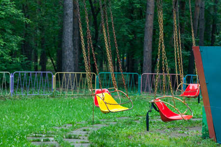 Multicolored yellow and red plastic seats hanging on the chains carousel in the park for entertainment and fun for children and adults against the background of green trees and grass. Stockfoto