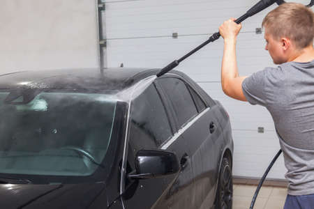 A male worker washes roof of a black car with a high-pressure apparatus from which water flows and washes away foam and chemicals in a vehicle delinging workshop. Auto service Industry.