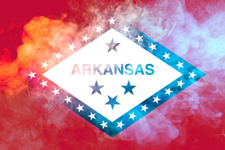 The national flag of the US state Arkansas in against a gray smoke on the day of independence in different colors of blue red and yellow. Political and religious disputes, customs and delivery. Фото со стока