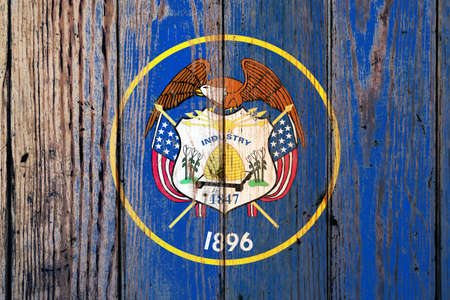 Utah US state national flag on a gray wooden boards background on the day of independence in different colors of blue red and yellow. Political and religious disputes, customs and delivery. 版權商用圖片
