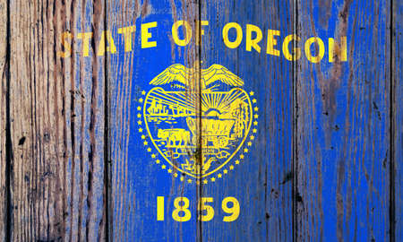 Oregon US state national flag on a gray wooden boards background on the day of independence in different colors of blue red and yellow. Political and religious disputes, customs and delivery.