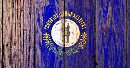 Kentucky US state national flag on a gray wooden boards background on the day of independence in different colors of blue red and yellow. Political and religious disputes, customs and delivery.