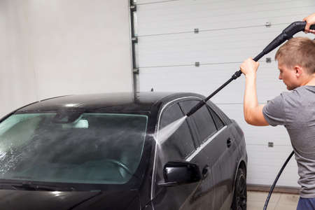 A male worker washes a black car with a high-pressure apparatus from which water flows and washes away foam and chemicals in a vehicle delinging workshop. Auto service Industry.