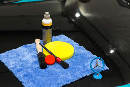 Novosibirsk, Russia - 07.20.2019: A set of tools for polishing and washing a car consisting of blue microfiber, a large yellow circle and a small red brush and a bottle with a paste on the hood Banque d'images - 127551030