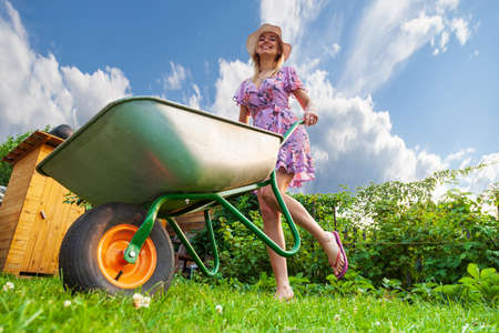 Young beautiful girl blonde in a dress and hat, having fun in the garden holding in her hands a green cart on the lawn with grass on the bushes background. Stok Fotoğraf