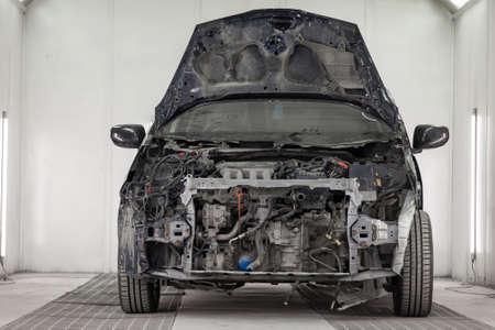 L'auto nera dopo un grave incidente con la parte anteriore completamente rotta della carrozzeria con il cofano aperto che è in attesa di riparazione in una stanza dell'officina per la verniciatura della carrozzeria dei veicoli. Industria dei servizi automobilistici