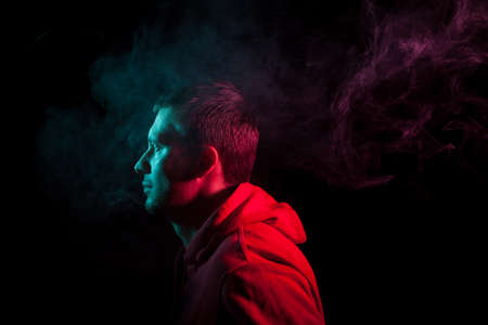 Portrait of a man in profile face looking towards a black isolated background with a sense of hope and dreaming, around head a cloud of blue and pink smoke. The soul and feelings of man.