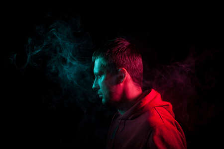 Portrait of a guy in profile face standing back to black background with a feeling of sadness and loneliness, around his head a cloud of blue and pink smoke. The soul and feelings of man