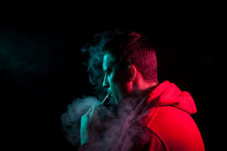 A young brunette man holds in his hand and drags on an electronic cigarette with a vape while smoking and releases smoke to the sides, his face is highlighted with red and green light.