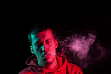 Close up portrait of the face of an adult serious man exhales pink toxic smoke while smoking e-cigarette and vape illuminated with blue and red colored light on a black background. Harm to health. Imagens