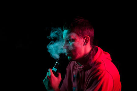 Close up portrait of the face of an adult serious man exhales green toxic smoke while smoking e-cigarette and vape illuminated with blue and red colored light on a black background. Harm to health. Imagens
