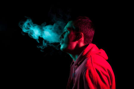 Close up portrait of the face of an adult serious man exhales green toxic smoke while smoking e-cigarette and vape illuminated with blue and red colored light on a black background. Harm to health.