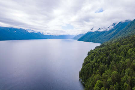 An aerial view of the Teletskoye Lake between the Altai Mountains on the shore on which there are green trees and other ships. Leisure and outdoor travel without people. Stok Fotoğraf