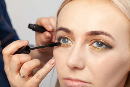 Makeup artist puts on an oriental-style make-up with gold and green shades of a young attractive blonde girl, paints her eyelashes with mascara, hold on the upper eyelid, holding a brush.
