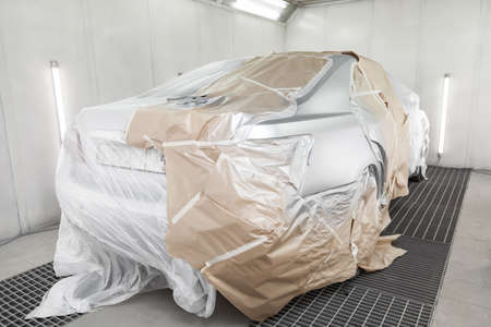 Painting silver car in auto service workshop. Car industry.