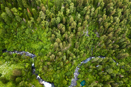 A large waterfall in the back of the Altai Mountains near a steep cliff with green trees, house and green roof. Rest and loneliness while traveling to deserted places. Aerial view Stok Fotoğraf