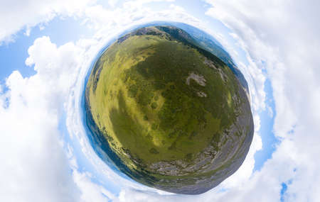 Aerial view of planet earth in the form of a nutlet with the image of nature and picturesque landscapes near a mountain with a rocky peak on a summer day with white clouds and blue sky. A small and defenseless planet. Banco de Imagens