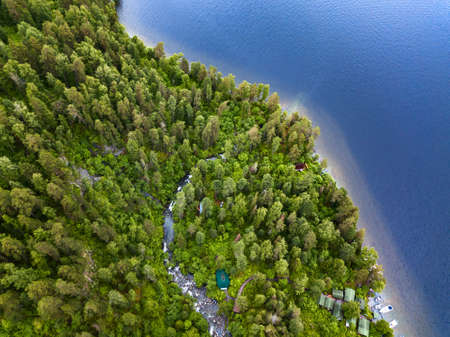 A large waterfall in the back of the Altai Mountains near a steep cliff with green trees, house, green roof. Beach, ships and boat. Rest and loneliness while traveling to deserted places. Aerial view