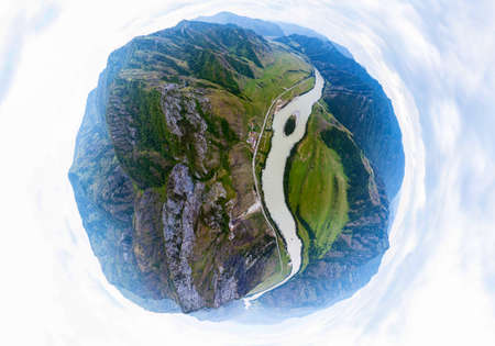Aerial view of planet earth with the image of nature and picturesque landscapes near a mountain with a river and green trees on a summer day in cloudy weather. A small and defenseless planet. Фото со стока