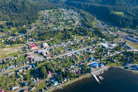 Aerial view of the pier in the Teletskoye lake with ships, ships and boats moored to the coast near the village of Artybash on a sunny summer day. Rest and travel to the nature reserve. Фото со стока