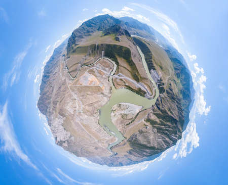 Aerial view of planet earth with the image of nature and picturesque landscapes near a mountain with a river and green trees on a summer day and blue sky. A small and defenseless planet. Фото со стока