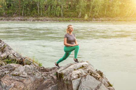 Blond pretty woman with tight booty is doing stretching by Lunging with your hands on the leg against the cliff in the picturesque place in mountains near the river and tree on stones. Standard-Bild