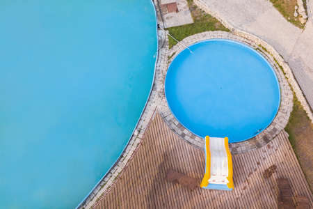 Aerial view from above of a small childrens pool with blue water next to a bouncy slide with wooden sunbeds and grass on a summer day while resting and relaxing. 新聞圖片