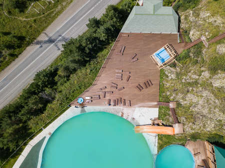 Aerial view of a tourist recreation center in with two swimming pools and wooden sun loungers on nature in the Altai mountains on a sunny warm day. Rest, tourism and vacation. Reklamní fotografie