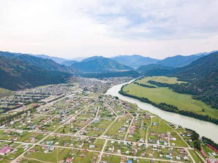 Privathäuser in einem Dorf oder in einem Cottage-Dorf zwischen grünen Bäumen und Gras in der Nähe des Flusses Katun im Altai-Gebirge an einem Sommertag Standard-Bild