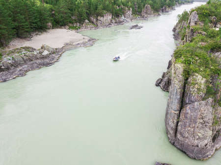 Aerial view of a rubber motor boat sailing on a green river in the mountains between rocks and cliff