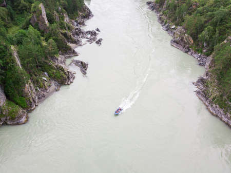 Aerial view of a rubber motor boat sailing on a green river in the mountains between rocks and cliff Imagens