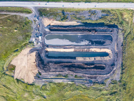 Aerial view of a quarry for the extraction and laundering of minerals with three pits filled with water surrounded by green grass. Environmental pollution.