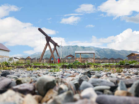 A playground in the yard with a swing made of wood against a picturesque landscape with mountains and a blue sky and clouds.