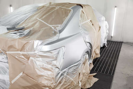 A large silver sedan car is completely covered in paper and adhesive tape to protect against splash during painting after an accident in a workshop for body repair of vehicles. Auto service industry.