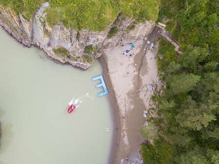 Aerial view of a rubber motor boat sailing from a blue plastic pier on a green river in the mountains Stock Photo