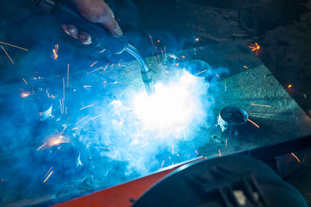 Semi-automatic spot welding of metal parts during the work of the master in the construction workshop with blue smoke and yellow sparks. Stockfoto