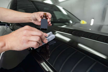 The process of applying a nano-ceramic coating on the cars hood by a male worker with a sponge and bottle with special chemical composition to protect the paint on the body from scratches, chips