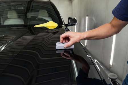 The process of applying a nano-ceramic coating on the cars hood by a male worker with a sponge and special chemical composition to protect the paint on the body from scratches, chips and damage.