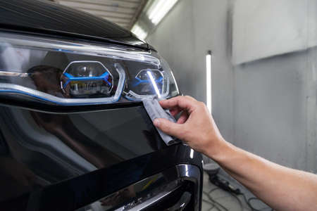 The process of applying a nano-ceramic coating on the cars bumper by a male worker with a sponge and special chemical composition to protect the paint on the body from scratches, chips and damage.