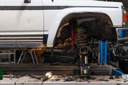 Car suspension repair in the back of a white SUV on a lift with a wheel removed and a disassembled suspension. Auto service industry and maintenance.